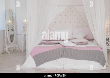 Big bed with cute pastel bedding in woman's room. Modern bedroom in pastel colors. four-poster bed.Scandinavian simplicity design. Eco loft apartments. - Stock Photo