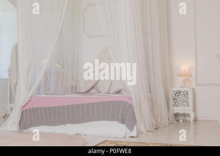 Bedroom in soft light colors with a wooden floor. Big comfortable four poster double bed in elegant classic bedroom. Natural white with wood interior design.Large bed. - Stock Photo