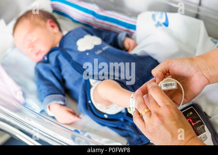 Using oximeter on newborn baby boy to check his level of oxygen in the hospital - Stock Photo