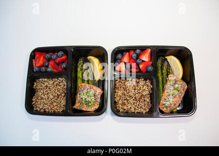 Planned meals in containers - salmon with asparagus, quinoa and fresh fruit. - Stock Photo