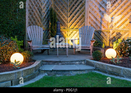 Beautiful, landscaped, private garden with contemporary design, borders & patio seating illuminated by globe lights at dusk - Yorkshire, England, UK. - Stock Photo