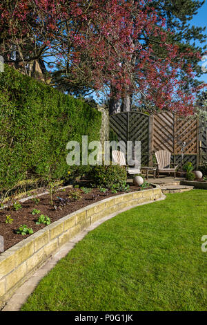 Sunny corner of beautiful, landscaped, private garden (contemporary design, border plants, patio seating, lawn & ornaments) - Yorkshire, England, UK. - Stock Photo