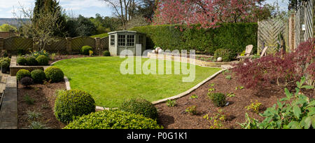 Beautiful, sunny, newly landscaped, private garden with contemporary design, border plants, patio seating, lawn & summerhouse - Yorkshire, England, UK - Stock Photo