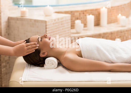 attractive woman relaxing and having head massage in massage salon - Stock Photo