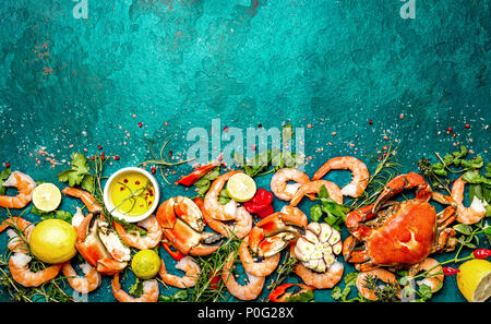 Fresh raw seafood - shrimps and crabs with herbs and spices on turquoise background. Copy space. - Stock Photo