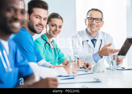 team of doctors and general practitioner having conversation and looking at camera - Stock Photo