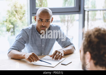 portrait of focused african american businessman listening to colleague at business meeting - Stock Photo