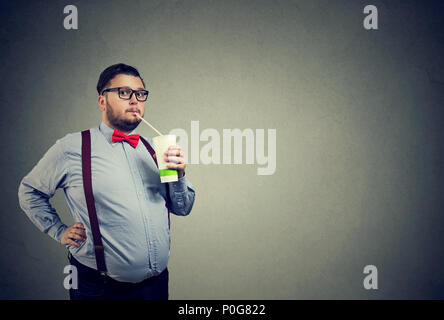 Formal chubby man in bow tie and glasses consuming sweet soda water looking at camera on gray - Stock Photo
