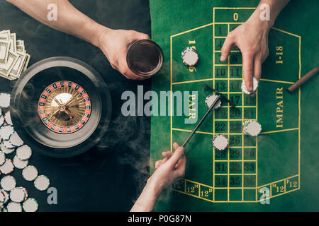 Smoke over people placing bets while playing roulette on casino table - Stock Photo