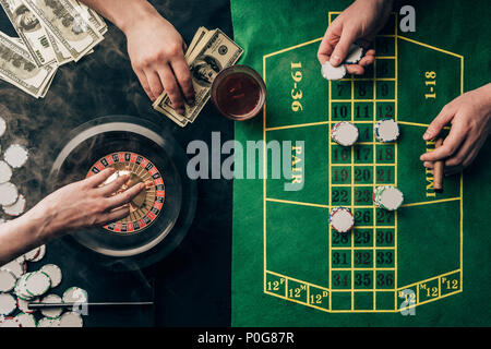 People placing bets while playing roulette on casino table - Stock Photo