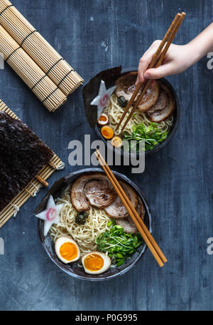 Hand with chopsticks try miso ramen - Stock Photo