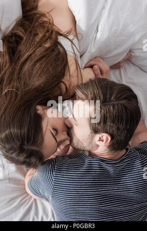 top view of young couple kissing in bed at morning - Stock Photo