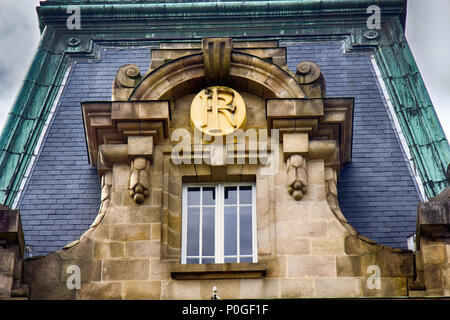 Limoges, France - September 28, 2017: Architectural details on building, aesthetic frills. Monogram of house owner under lush canopy of stone - Stock Photo