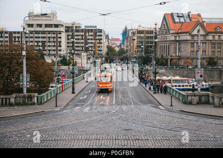 Prague, September 24, 2017: A tram and a lot of cars follow him on the bridge. Nearby people walk on the pedestrian side of the road. Ordinary city li - Stock Photo