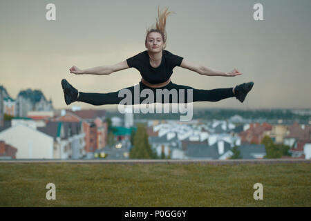 Young caucasian girl performs twine jumping over background cityscape - Stock Photo