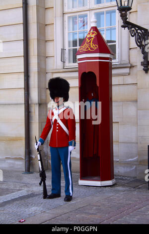 Copenhagen, Denmark, March 16, 2010: The guards of honour in red galla uniform guarding the Royal residence Amalienborg Palace - Stock Photo