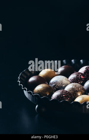 closeup view of pile of different chocolate candies in bowl on black background - Stock Photo