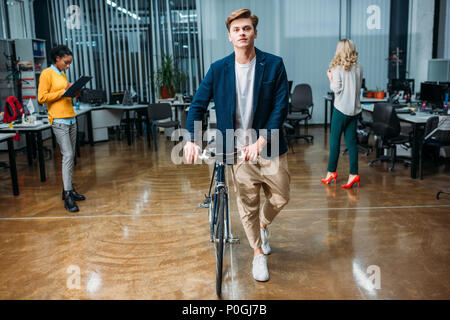 handsome young businessman with bike walking by modern office - Stock Photo