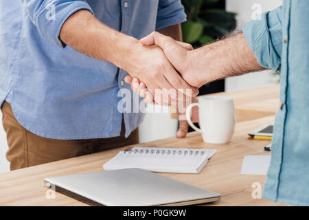cropped shot of businessmen shaking hands after meeting at workplace - Stock Photo