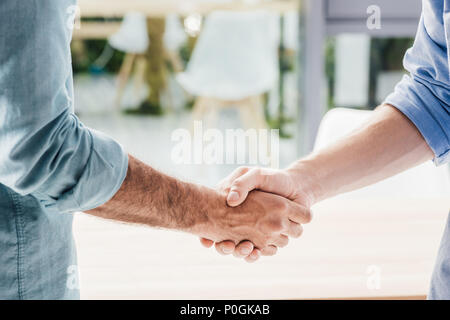cropped shot of businessmen shaking hands after meeting in office - Stock Photo