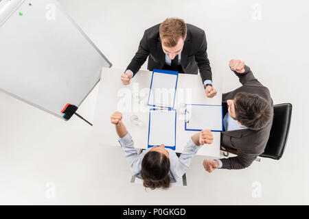overhead view of excited business people celebrating triumph during discussion at meeting isolated on white - Stock Photo