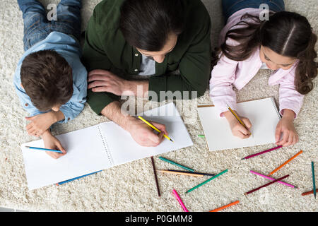 overhead view of father with children drawing with colored pencils at home - Stock Photo