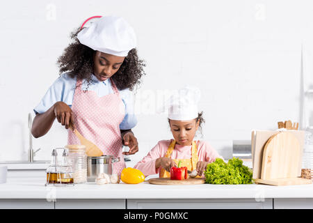 african american mother and daughter in chef hats cooking on kitchen - Stock Photo