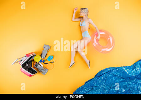 young woman in swimsuit and flip flops holding swimming ring on imagine beach, summer vacation concept - Stock Photo