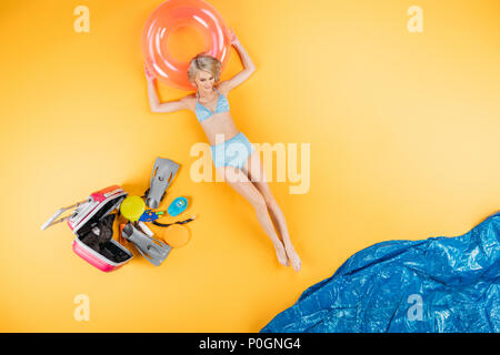 top view of beautiful young woman lying on inflatable ring on yellow, summer vacation concept - Stock Photo