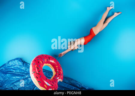 girl with swimming ring diving in imagine sea on blue, summer vacation concept - Stock Photo