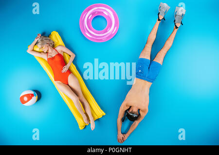 top view of young couple resting with beach items on blue, summer vacation concept - Stock Photo