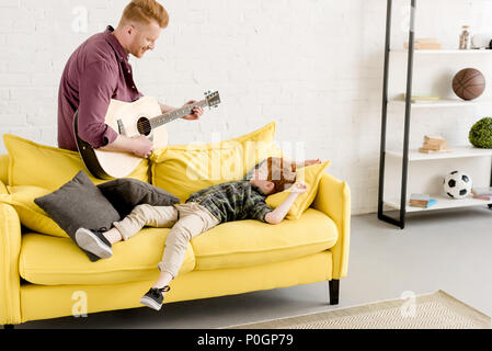 smiling father playing guitar and cute little son lying on couch