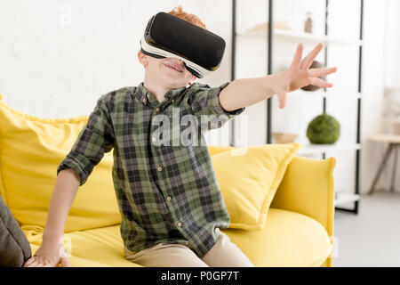adorable smiling little boy using virtual reality headset at home - Stock Photo