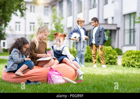 adorable multiethnic schoolgirls sitting on bean bag chair and reading book while schoolboys standing with soccer ball on schoolyard - Stock Photo