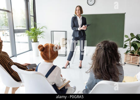 young female teacher explaining lesson to students in classroom - Stock Photo