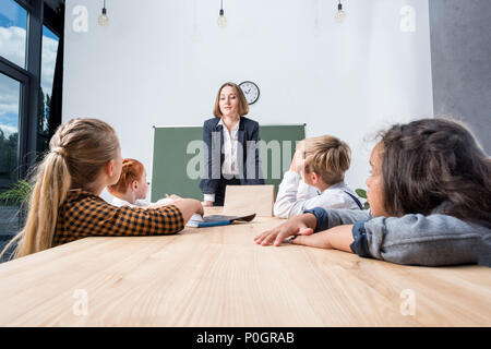 smiling young teacher leaning at desk and looking at cute multi ethnic children in classroom - Stock Photo