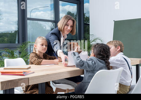 young female teacher working with cute little schoolchildren in classroom - Stock Photo