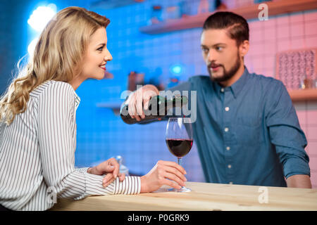 handsome bearded bartender pouring red wine to smiling blonde woman in bar - Stock Photo
