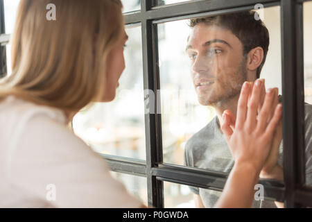 side view of couple in love looking at each other through glass door in cafe - Stock Photo