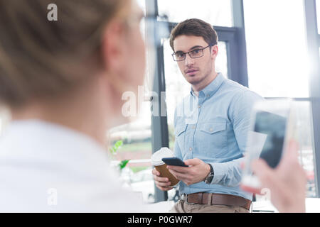 businessman using smartphone with colleague on foreground in modern office - Stock Photo