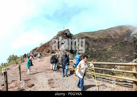 People walking up Vesuvius, Mount Vesuvius or Vesuvio, an active volcano that rises above the Bay of Naples on the plain of Campania in Italy - Stock Photo