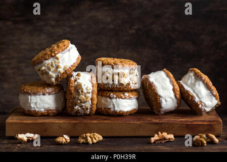 Ice cream sandwiches with nuts and wholegrain cookies. Homemade vanilla ice cream sandwiches on dark wooden background. - Stock Photo