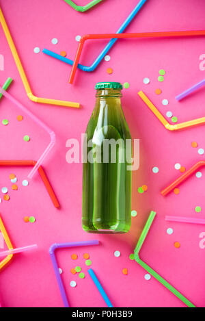 Cold green drink with straws and confetti on bright pink background and copy space for text. Summer party, happy vacation and fun concept, top view. - Stock Photo