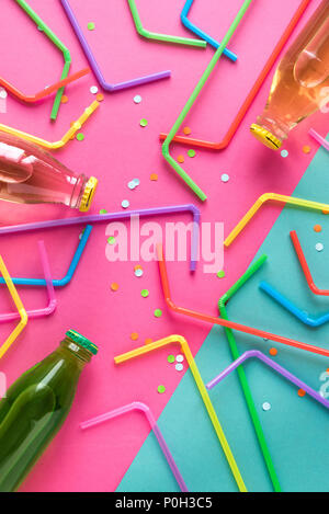 Various cold drinks with straws and confetti on pink and blue background. Summer party, happy vacation and fun concept, top view. - Stock Photo
