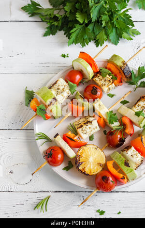 Vegetarian grilling. Vegetarian skewers with halloumi cheese and vegetables on white background, copy space. - Stock Photo