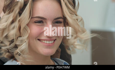 Hairdresser shake curled hair making hair style more natural - Stock Photo