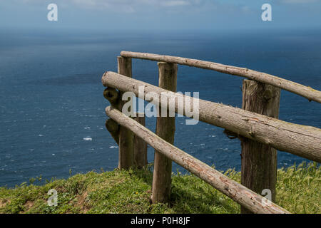 Wooden natural fence on an edge of  green meadow with a fresh grass. View on the Atlantic ocean. Sao Miguel, Azores Islands, Portugal. - Stock Photo