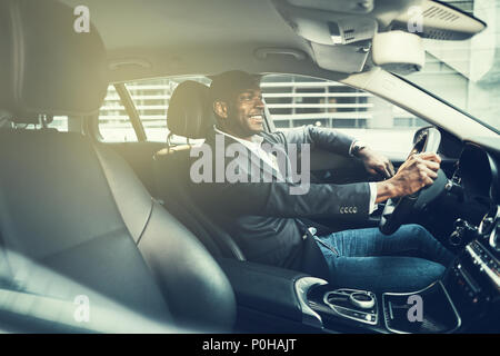 African businessman wearing a blazer and smiling while driving his car to work during his morning commute - Stock Photo