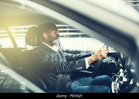 African businessman wearing a blazer and smiling while driving his car through city traffic during his morning commute - Stock Photo