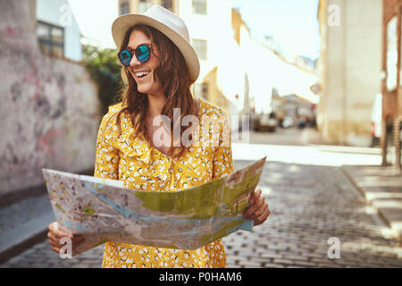 Smiling young brunette woman exploring the cobblestone streets of a city with a map while on vacation - Stock Photo